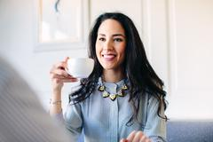 Young woman drinking coffee in boutique hotel in Italy - stock photo