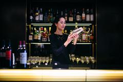Young barmaid preparing cocktail in boutique hotel cocktail bar Stock Photos