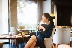Young woman staying in boutique hotel enjoying aperitif Stock Photos