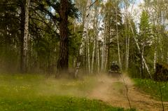 Rear view of man quadbiking on dusty forest dirt road, Russia - stock photo