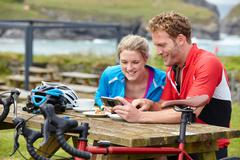 Cyclists using mobile phone at picnic table overlooking ocean - stock photo