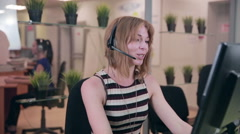 Frendly woman talking on the headset in an office, call centre - stock footage