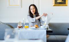Young woman preparing napkin whilst having champagne breakfast at  boutique Stock Photos