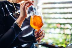 Cropped shot of young woman drinking spritz cocktail in boutique hotel - stock photo