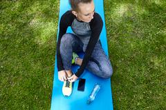 Young woman training in park, tying trainer laces on exercise mat Stock Photos