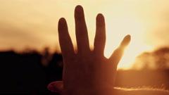 Hand stroking sun stroke sun at sunset Stock Footage