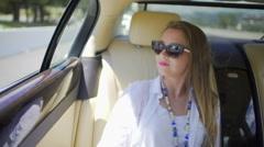 Pretty blonde woman enjoying trip on backseat of expensive auto, tourism Stock Footage