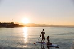 Silhouette of perfect couple engage standup paddle boarding Stock Photos