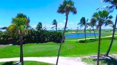 Aerial - Beautiful view of Golf Course next to ocean going up next to palm tr Stock Footage