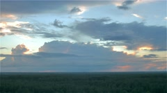 Sun hides behind storm rain cloud over green summer forest. aerial timelapse Stock Footage