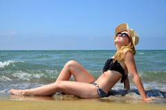 Caucasian girl with hat on the beach. Stock Photos