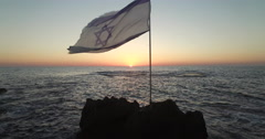 Aerial of Israeli flag on small rock at Mediterranean sea Stock Footage