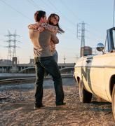 Couple hugging by convertible classic car, Los Angeles, California, USA Stock Photos