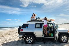 Two young girls untying surfboards from top of car Stock Photos