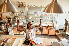 Woman at desk in pottery studio with paperwork, arms raised smiling Stock Photos