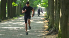 Sportsman stretch in the beautiful park alley. Slow motion. Super telephoto lens Stock Footage