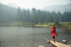 Woman wrapped in tartan blanket drinking coffee by misty lake, Mount Hood - stock photo