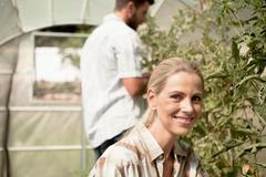 Mature couple tending to plants in greenhouse Stock Photos