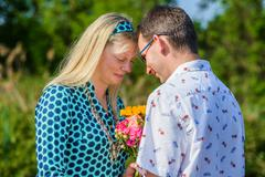 Couple face to face holding flowers Stock Photos