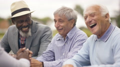 4K Happy senior male friends chatting & laughing together outdoors in the park Stock Footage