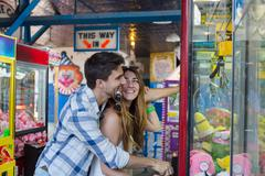 Couple at amusement park using arcade grabber, Coney island, Brooklyn, New York, Stock Photos