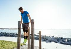 Man training, doing push ups on exercise bar at coast, downtown San Diego, - stock photo