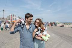 Couple holding cuddly toy cows smiling, Coney island, Brooklyn, New York, USA - stock photo