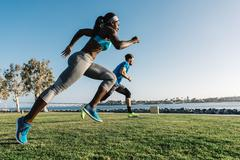 Man and young woman training, sprinting on coast, downtown San Diego, Stock Photos