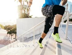 Waist down view of man training, running up stairway at sport facility, downtown - stock photo