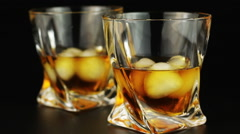 Young man drinking whiskey with ice over black background - stock footage