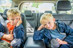 Twin brothers sitting in back of vehicle, bored expressions - stock photo