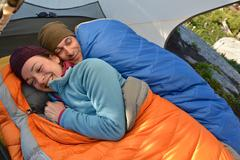 Happy couple in sleeping bags in tent at Fault Lake, Selkirk Mountains, Idaho - stock photo