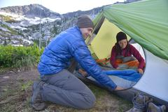 Couple putting sleeping bag in tent at Fault Lake, Selkirk Mountains, Idaho - stock photo