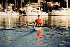 Young man rowing single scull on Puget Sound, Winslow, Bainbridge Island, - stock photo