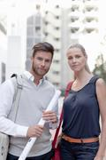 Portrait of man and woman outdoors, man holding rolled up documents Stock Photos