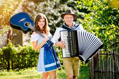 Couple in traditional bavarian clothes with guitar and accordion Kuvituskuvat
