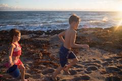 Boy and sister running on beach, Blowing Rocks Preserve, Jupiter Island, - stock photo