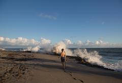 Rear view of boy exploring beach with splashing waves, Blowing Rocks Preserve, Stock Photos