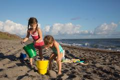 Two sisters playing with toy buckets on beach, Blowing Rocks Preserve, Jupiter - stock photo