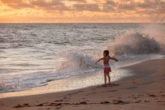 Girl with arms open whilst waves splash at sunrise, Blowing Rocks Preserve, Stock Photos