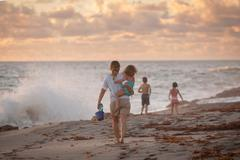 Mother carrying daughter on beach at sunrise, Blowing Rocks Preserve, Jupiter - stock photo
