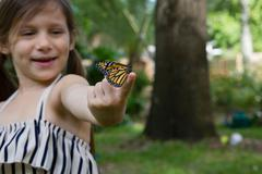 Girl holding monarch butterfly on finger smiling - stock photo