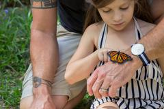 Father and daughter looking at monarch butterfly - stock photo