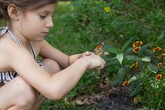 Girl crouching holding monarch butterfly - stock photo