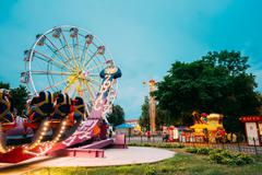 Attraction Zodiac With People Going Start. Ferris Wheel Evening Stock Photos