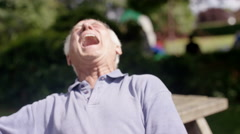 4K Portrait very happy senior man sitting in the park & laughing Stock Footage