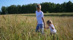 Children walk through a wheat field Stock Footage