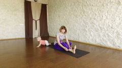 The young girl practicing yoga with child in a hall. The incline to the legs. 4K Stock Footage