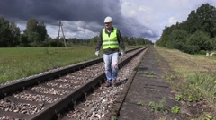Railroad worker with cell phone and adjustable wrench walking near railway Stock Footage
