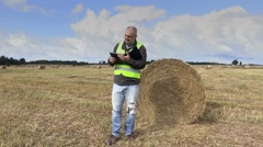 Farmer on the field near straw bale Stock Footage